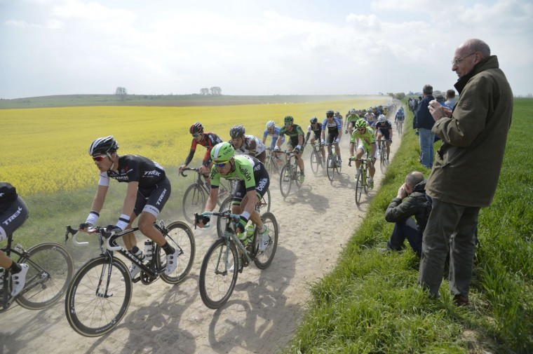 Spectators watch the pack of riders pedaling through a cobblestoned section during the 112th edition of the Paris-Roubaix one-day classic cycling race between Compiegne and Roubaix, northern France. (Eric Feferberg/Getty Images)