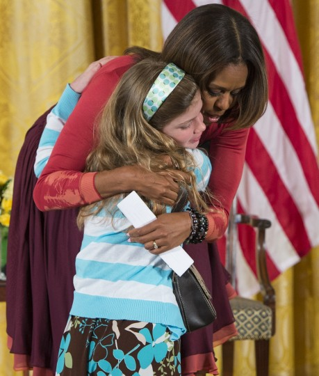 US First Lady Michelle Obama hugs Charlotte Bell, 10, after she gave Obama a copy of her father's resume, who has been out of work for 3 years, as Obama answered questions from children of Executive Office employees at the White Houses annual Take Our Daughters and Sons to Work Day in the East Room of the White House in Washington, DC, April 24, 2014. (Saul Loeb//AFP/Getty Images)