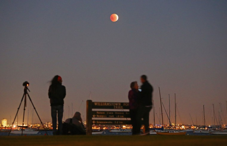 People watch as the 'Blood Moon' rises over the water in Wlliamstown on April 15, 2014 in Melbourne, Australia. (Photo by Scott Barbour/Getty Images)