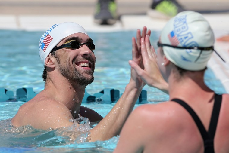 Michael Phelps (L) high fives Allison Schmitt as they warm up in the practice pool during day one of the Arena Grand Prix at the Skyline Aquatic Center on April 24, 2014 in Mesa, Arizona. (Photo by Christian Petersen/Getty Images)