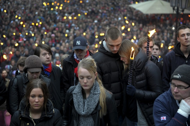 People gather against soccer violence around a makeshift memorial with flowers, candles and club scarfes at the spot in central Helsingborg, southern Sweden, on March 31, 2014, where a Djurgarden IF supporter got assaulted and died of his head injuries before the season opening Swedish league match between Helsingborg IF and Djurgarden IF held at Olympia in Helsingborg on March 30. (Bjorn Lindgren/TT/AFP/Getty Images)