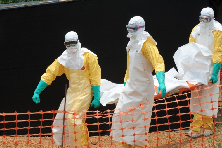 Staff of the 'Doctors without Borders' ('Medecin sans frontieres') medical aid organisation carry the body of a person killed by viral haemorrhagic fever, at a center for victims of the Ebola virus in Guekedou, on April 1, 2014. The viral haemorrhagic fever epidemic raging in Guinea is caused by several viruses which have similar symptoms -- the deadliest and most feared of which is Ebola. (Seyllou/AFP/Getty Images)