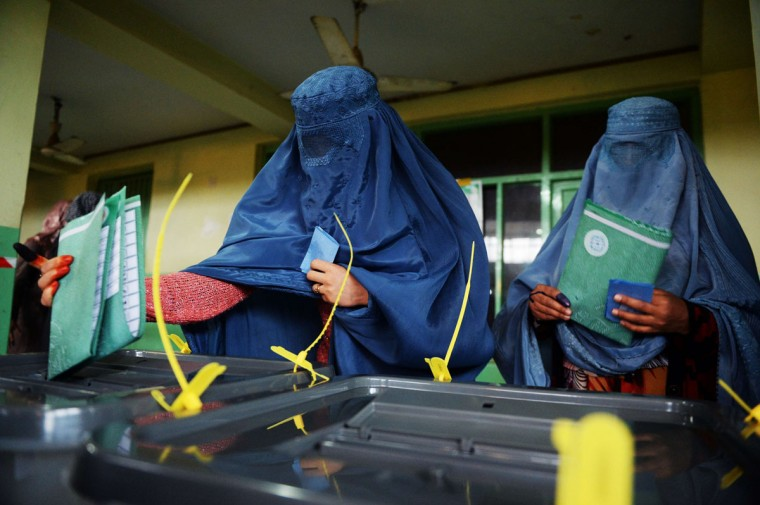 Afghan women cast their ballots at a local polling station in Kabul on April 5, 2014. Afghan voters went to the polls to choose a successor to President Hamid Karzai, braving Taliban threats in a landmark election held as US-led forces wind down their long intervention in the country. Afghanistan's third presidential election brings an end to 13 years of rule by Karzai, who has held power since the Taliban were ousted in a US-led invasion in 2001, and will be the first democratic handover of power in the country's turbulent history. (Shah Marai/AFP/Getty Images)