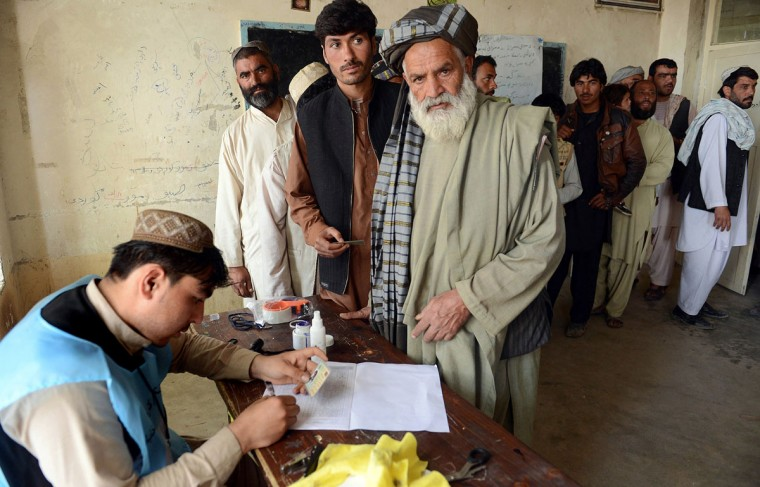 An Afghan election official notes a voter's identification card at a local polling station in Kandahar on April 5, 2014. Afghan voters went to the polls to choose a successor to President Hamid Karzai, braving Taliban threats in a landmark election held as US-led forces wind down their long intervention in the country. (Banaras Khan/AFP/Getty Images)