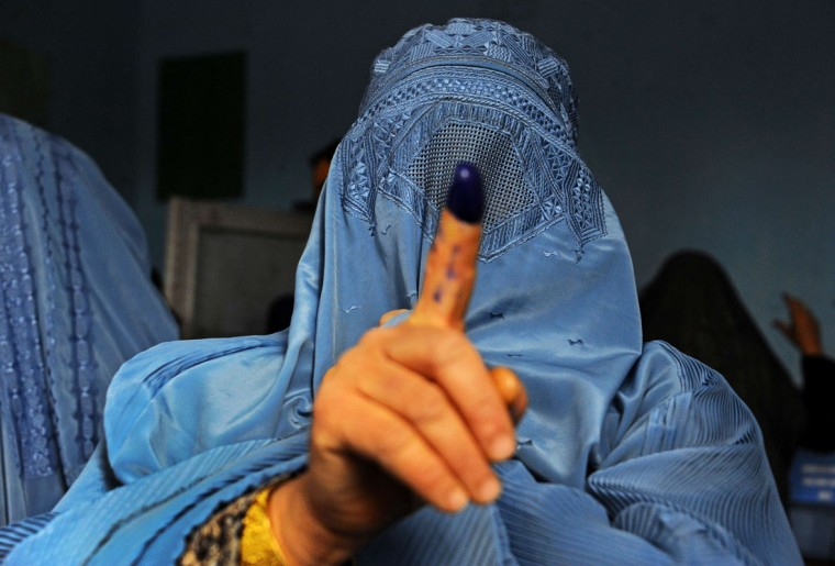 An Afghan woman shows her inked finger after voting at a polling station in the northwestern city of Herat on April 5, 2014. Afghan voters went to the polls to choose a successor to President Hamid Karzai, braving Taliban threats in a landmark election held as US-led forces wind down their long intervention in the country. (Aref Karimi/AFP/Getty Images)