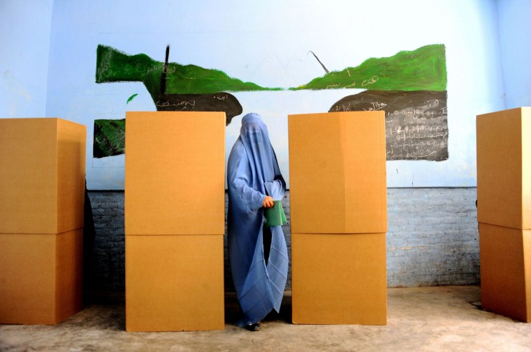An Afghan woman leaves the booth after casting her vote at a polling station in the northwestern city of Herat on April 5, 2014. Afghan voters went to the polls to choose a successor to President Hamid Karzai, braving Taliban threats in a landmark election held as US-led forces wind down their long intervention in the country. (Aref Karimi/AFP/Getty Images)
