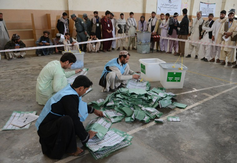 Afghan election officials count ballot papers at the end of polling in Kandahar on April 5, 2014. Afghans voted in large numbers to choose a successor to President Hamid Karzai in the country's first democratic transfer of power as US-led forces end their 13-year war. (Banaras Khan /AFP/Getty Images)