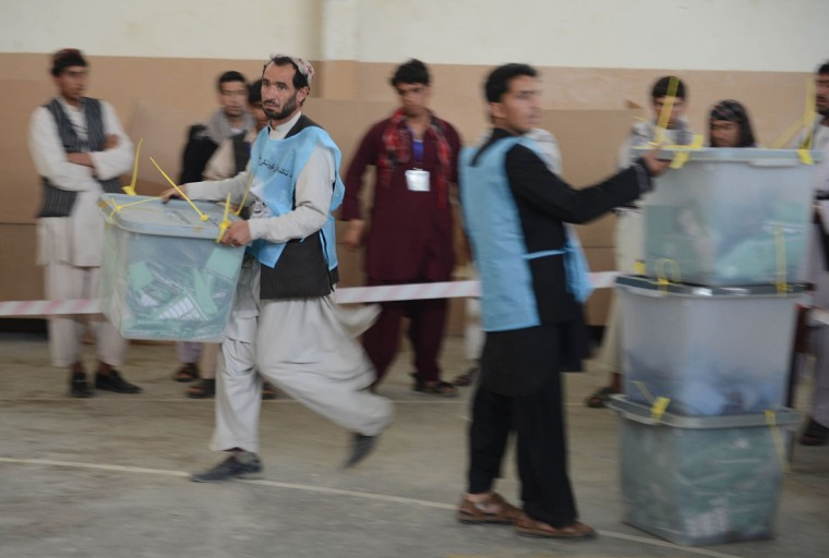 An Afghan election official (L) carries a ballot box before counting at the end of polling in Kandahar on April 5, 2014. Afghans voted in large numbers to choose a successor to President Hamid Karzai in the country's first democratic transfer of power as US-led forces end their 13-year war. (Khan BanarasAFP/Getty Images)