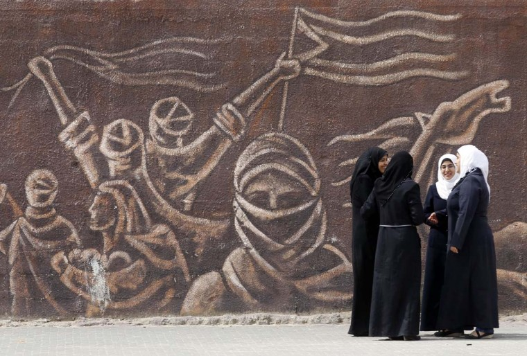 Palestinian schoolgirls stand in front of a mural during an awareness training session on dangers of unexploded ordnance on April 7, 2014 at a school in Khan Younis in the southern Gaza Strip. (Said Khatib/AFP/Getty Images)