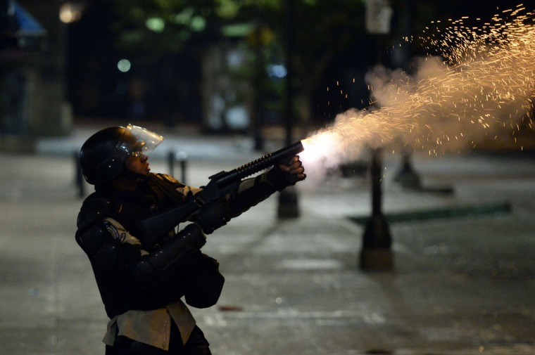 A member of the National Police shoots tear gas during clashes with anti-government demonstrators in Caracas on April 7, 2014. Venezuelan President Nicolas Maduro agreed to meet with a Venezuelan opposition delegation on Tuesday, after a fresh push from top diplomats from across South America. In just over two months, 39 people have died in clashes between security forces and protesters angered by soaring crime, high inflation and shortages demonstrators blame on Maduro's elected, heavily state-led socialist government. (Juan Barreto/AFP/Getty Images)