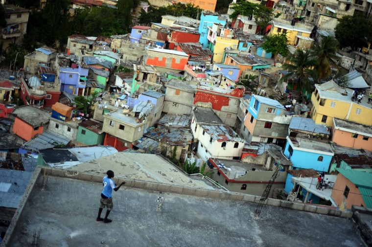 """A child plays with a kite on the roof of a house at the neighborhood of """"Jalousie"""" in the Petion-Ville comune, in Port au Prince, on April 7, 2014. (Hector Retamal/AFP/Getty Images)"""