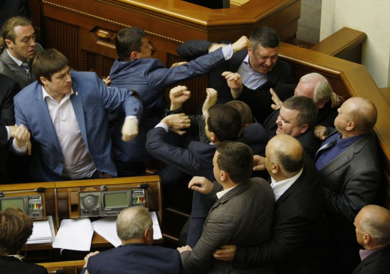 "Members of Parliament of the Svoboda party fight with Members of Parliament of the Communist party in the Ukrainian parliament on April 8, 2014, during the debates focused on a law toughening responsibility for separatism. Ukraine's acting president said today he would treat Russian separatists who have seized buildings in the east of the country as ""terrorists"" who will be prosecuted with the full force of the law. (Yuriy Kirnichny/AFP/Getty Images)"