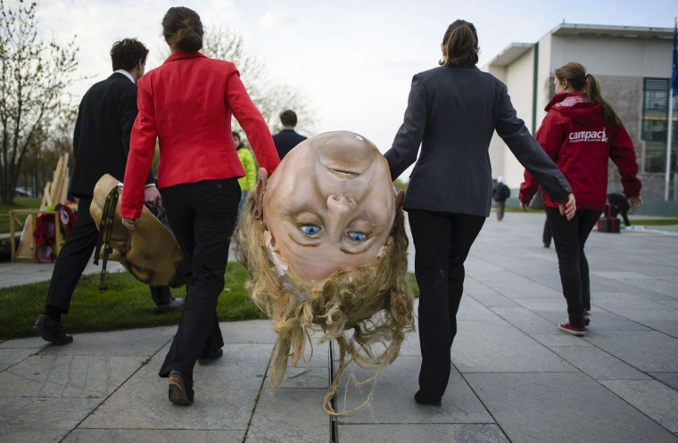 Activists of BUND and Campact ecological associations carry a giant head featuring German Chancellor Angela Merkel before a demonstration against the reform of the Renewable Energy Sources Act (EEG). Berlin is implementing a deep reform of its system of subsidies for clean energy, currently the cornerstone of the country's energy transition. (Clemens Bilan/AFP/Getty Images)
