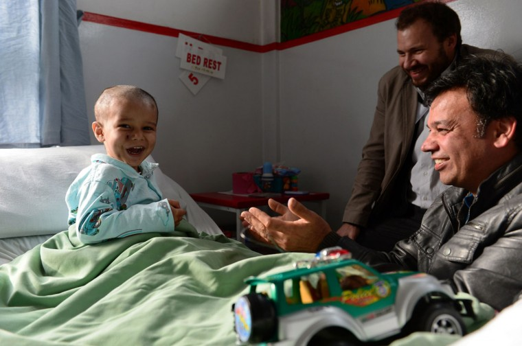 """Abuzar Ahmad, the youngest son of slain Afghan AFP reporter Sardar Ahmad, plays during a visit by his uncle Bashir Mirzad (R) and AFP Bureau Chief for Pakistan-Afghanistan Emmanuel Duparcq (C) at a local hospital in Kabul. The orphaned Afghan child whose family was gunned down in a luxury Kabul hotel may soon leave hospital after recovering rapidly from bullet wounds to his skull, chest and thigh, doctors said. Abuzar Ahmad, aged two years and 11 months, suffered fragment wounds in the shooting on March 20 that killed his father, senior AFP reporter Sardar Ahmad, mother Homaira, sister Nilofar, 6, and brother Omar, 5. Abuzar's relatives hope that he will start a new life with many of his cousins who live in Toronto, Canada. """"He could be discharged within a week or 10 days if things continue to go well,"""" Luca Radaelli, medical coordinator at the Italian-run Emergency Hospital in Kabul, told AFP. (Wakil Kohsar/AFP/Getty Images)"""