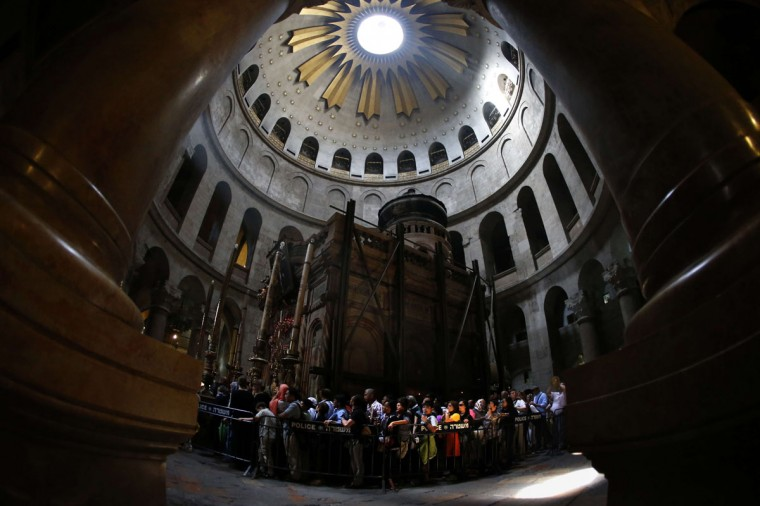 """Christian pilgrims gather around the """"Edicule of the Tomb of Jesus Christ"""" in The Church of the Holy Sepulchre, also known as the Basilica of the Resurrection, one of Christianity's holiest sites in Jerusalem's old city on April 7, 2014. Christians traditionally believe the church is built on the site where Jesus was crucified, buried and resurrected. (Thomas Coex/AFP/Getty Images)"""