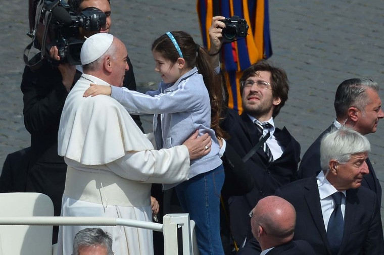 A girl jumps on the papamobile to hug Pope Francis at the end of the Palm Sunday celebrations at St Peter's square on April, 2014 at the Vatican. (Vincenzo Pinto/AFP/Getty Images)