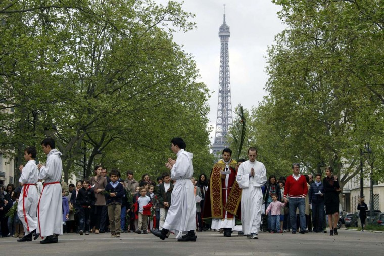 A priest, accompanied by altar boys, carries a palm branch on April 13, 2014 during Palm sunday celebrations in the center of Paris with the Eiffel Tower in the background. The ceremony is a landmark in the Christian calendar, marking the triumphant return of Christ to Jerusalem the week before his death, when a cheering crowd greeted him waving palm leaves.(Ludovic Marin/ AFP/Getty Images)