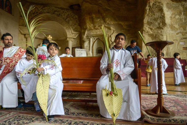 Orthodox Christian alter boys hold fans made of palm leaves during the Palm Sunday service on April 13, 2014 in Cairo, to celebrate the triumphant return of Jesus Christ to Jerusalem when a cheering crowd greeted him waving palm leaves the week before his death. (Mohamed El-Shahed/AFP/Getty Images)