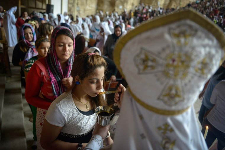 Orthodox Christians receive communion during the Palm Sunday service on April 13, 2014 in Cairo, to celebrate the triumphant return of Jesus Christ to Jerusalem when a cheering crowd greeted him waving palm leaves the week before his death. (Mohamed El-Shahed/AFP/Getty Images)