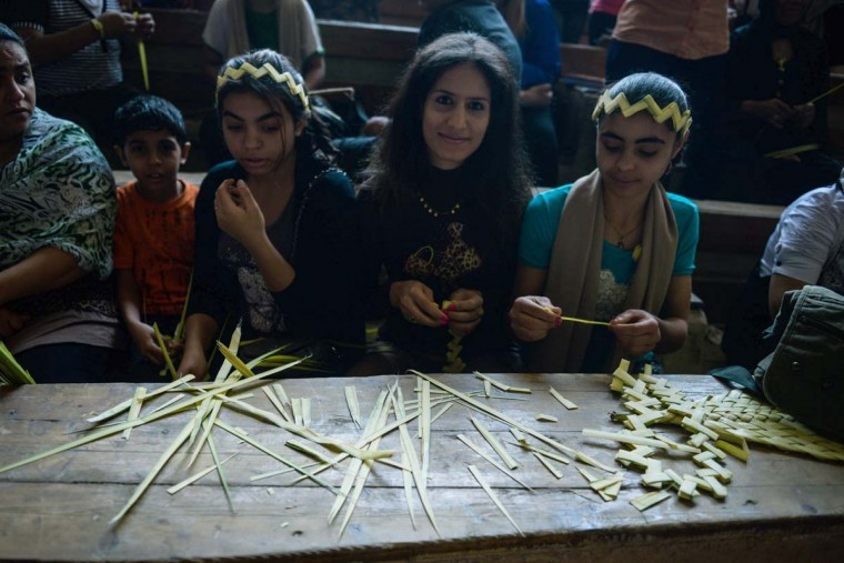 Orthodox Christians create palm leaf ornaments during the Palm Sunday service on April 13, 2014 in Cairo, as Christians celebrate the triumphant return of Jesus Christ to Jerusalem when a cheering crowd greeted him waving palm leaves the week before his death. (Mohamed El-Shahed/AFP/Getty Images)
