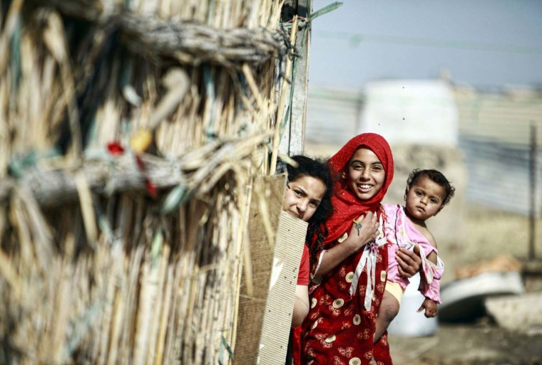 Young women look out from a hut in an agricultural area south of Iraq's central Shiite Muslim Shrine city of Najaf on April 14, 2014.(Haidar Hamdani/AFP/Getty Images)