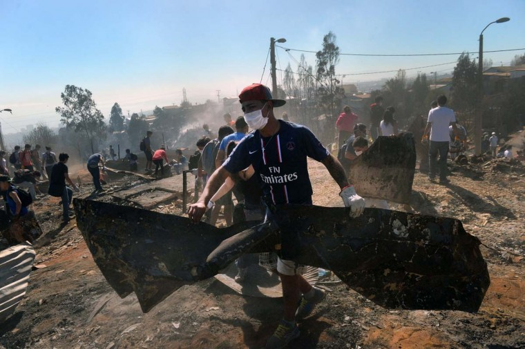 Volunteers help after a huge fire devastated an area of Valparaiso, Chile, on April 14, 2014. Firefighters backed by police and soldiers Monday battled for a third day a massive blaze that killed 12 people and ravaged a huge swath of Chile's historic port city of Valparaiso. It could yet be another two or three days before they succeed in extinguishing the fire, officials warned, the worst to hit the city, consuming 2,000 homes and forcing thousands of people to flee for their lives. Some people who refused to leave their homes were killed when the inferno swept it. (Martin Bernetti/AFP/Getty Images)