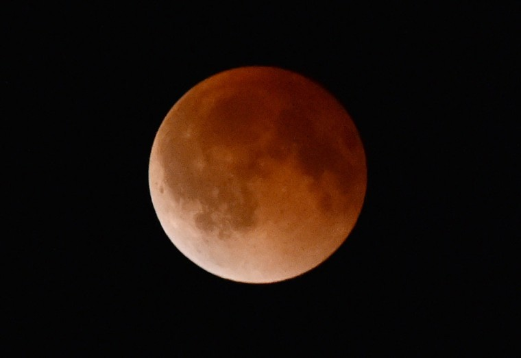 The moon turns a reddish color in the Earth's shadow during a total lunar eclipse April 15, 2014 as seen from Magdalena, New Mexico. (STAN HONDA/AFP/Getty Images)