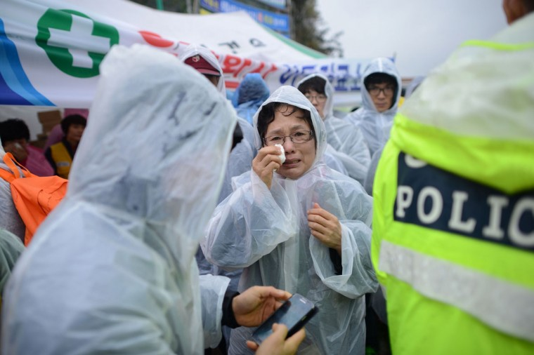 A relative (C) reacts as she waits in a makeshift tent along a dockside in Jindo on April 17, 2014, as the frantic search for nearly 300 people, most of them schoolchildren, missing after a South Korean ferry capsized extended into a second day, as distraught relatives maintained an agonising vigil on shore. Heart-wrenching messages of fear, love and despair, sent by high school students from a sinking South Korean ferry added extra emotional weight on April 17 to a tragedy that has stunned the entire nation. (Ed Jones/AFP/Getty Images)