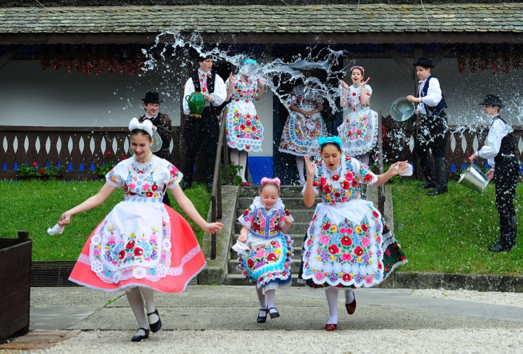 "Some local school girls in traditional clothes of the Kalocsa area react as boys throw water in Kalocsa, some 100 km south of Budapest on April 17, 2014 during a rehearsal of the traditional Easter celebrations by the members of the local folk dance group. Locals from south Hungary celebrate Easter with the traditional ""watering of the girls"", a fertility ritual rooted in Hungary's tribal pre-Christian past, going as far back as the second century AD. (Atilla Kisbenedek/AFP/Getty Images)"