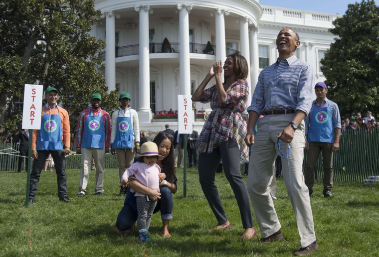 """US President Barack Obama and First Lady Michelle Obama react to a child rolling an Easter egg during the annual White House Easter Egg Roll on the South Lawn of the White House in Washington, DC, April 21, 2014. The 126th annual White House Easter Egg Roll, the largest annual public event at the White House with more than 30,000 attendees expected, features live music, sports courts, cooking stations, storytelling and Easter egg rolling, with the theme, """"Hop into Healthy, Swing into Shape."""" (Saul Loeb/AFP/Getty Images)"""