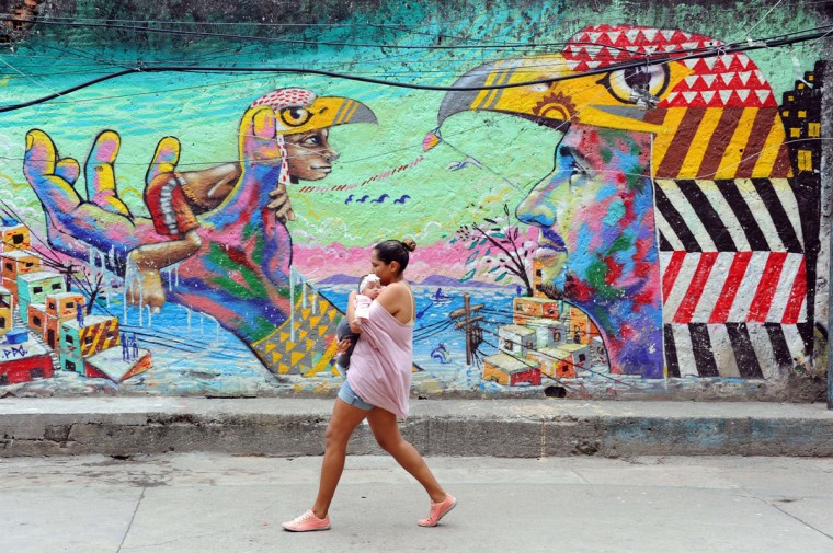 A local and her baby walk in the streets of the Cantagalo favela, next to Copacabana, where a young dancer was killed last weekend and residents held a protest on the eve, on April 23, 2014, in Rio de Janeiro. Just 50 days before Brazil hosts the World Cup, authorities beefed up security Wednesday in Rio de Janeiro after a violent clash between residents and police in a slum near the tourist haven of Copacabana beach. (Tasso Marcelo/AFP/Getty Images)