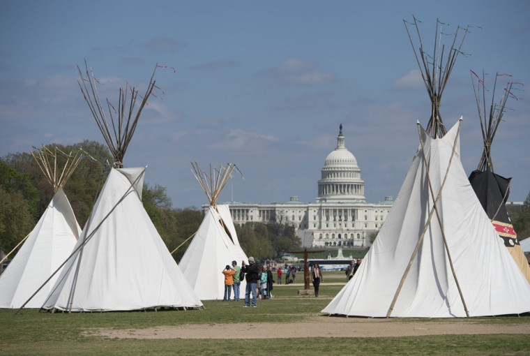Tourists walk around teepees set up on the National Mall in Washington, DC, April 23, 2014, as part of a weeklong demonstration by farmers, ranchers and tribes with the Cowboy and Indian Alliance, to protest against the Keystone XL pipeline. (Saul Loeb/AFP/Getty Images)