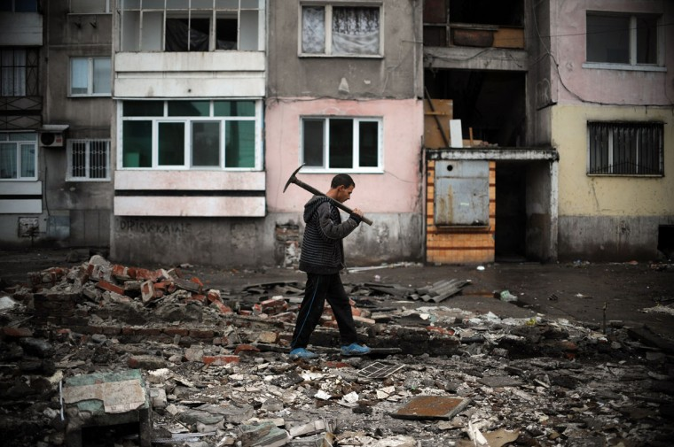 A Roma man walks with a pickaxe in the remains of a house demolished by a bulldozer in a Roma suburb in the city of Plovdiv on April 25, 2014. About fifty illegally built Roma houses and buildings were destroyed in the city of Plovdiv on Friday. Bulgaria's 700,000-strong Roma minority is highly ghettoised and discriminated against, and violent incidents -- both between Roma and between Roma and non-Roma -- are frequent. (Nikolay Doychinov/AFP/Getty Images)