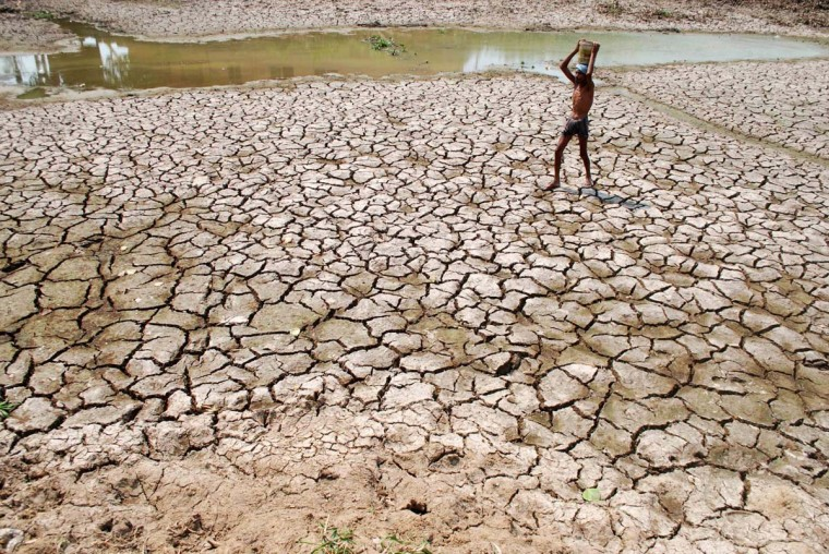 An Indian man carries a container of water on his head as he walks in a dry pond in a hot afternoon on the outskirts of eastern Bhubaneswar on April 28, 2014. Many Indian cities face severe water scarcity especially in the summer season as summer temperatures soar above the 40 degrees celsius. (Asit Kumar/AFP/Getty Images)