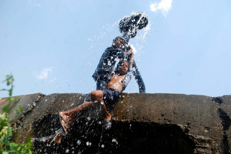 Indian children cool off as water water flows from a water supply pipeline to beat the heat on a hot afternoon on the outskirts of eastern Bhubaneswar on April 28, 2014. Many Indian cities face severe water scarcity especially in the summer season as summer temperatures soar above the 40 degrees celsius. (Asit Kumar/AFP/Getty Images)