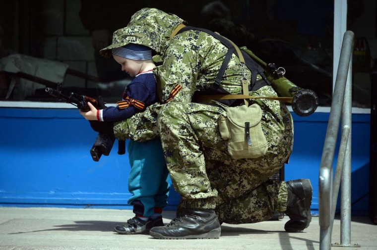 A pro-Russian armed man in military fatigues poses for a photograph with a child as he stands guard outside a regional administration building seized in the night by pro-Russian separatists, in the eastern Ukrainian city of Kostyantynivka, on April 28, 2014. The United States moved to impose fresh sanctions against Russia today over the crisis in Ukraine, as pro-Kremlin gunmen seized another town in the east, further escalating tensions. (Vasily Maximov/AFP/Getty Images)