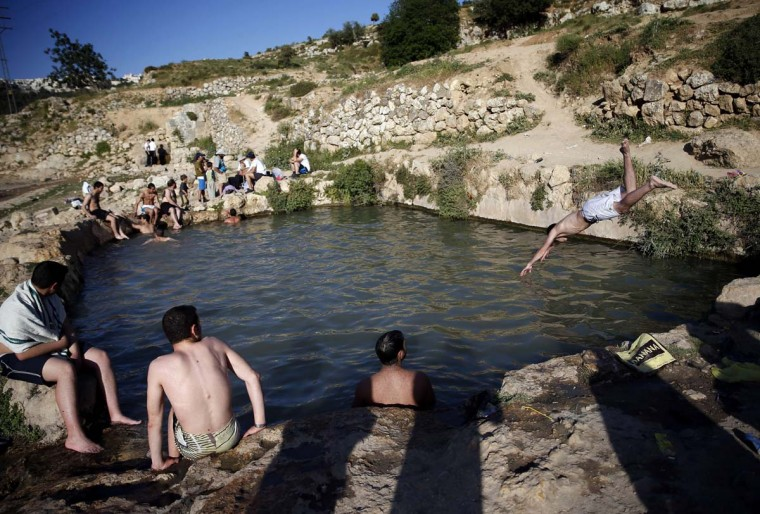 Orthodox Jewish men enjoy a natural swimming pool near the West Bank Palestinian village of Beit Jala, south of Jerusalem, on April 28, 2014. (Thomas Coex/AFP/Getty Images)