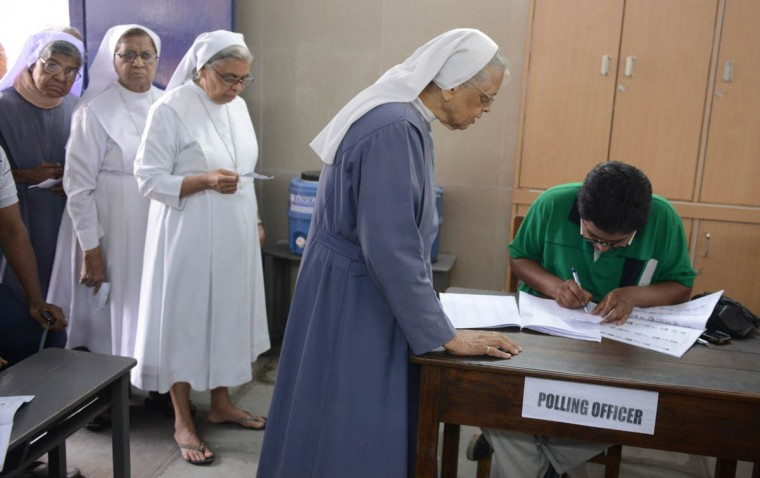 Indian catholic nuns checks their names with election commission officials as they wait to cast their votes at a polling booth in Hyderabad. India's 814-million-strong electorate is voting in the world's biggest election which is set to sweep the Hindu nationalist opposition to power at a time of low growth, anger about corruption and warnings about religious unrest. (Noah Seelam/Getty Images)
