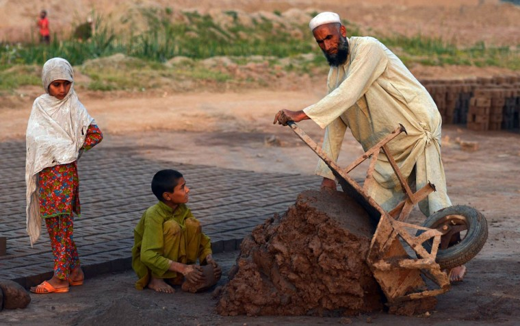 A Pakistani labourer empties a wheelbarrow loaded with clay to make bricks at a factory on the eve of International Labour Day in Peshawar. Pakistan has a workforce of around 56 million people in a population of 186 million, according to Pakistan's official figures compiled by the Federal Bureau of Statistics. (A Majeed/Getty Images)