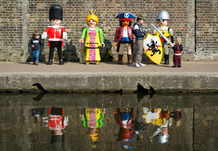 Children play with giant Playmobil figures during a photocall on the canalside at Camden in north London as the toy company celebrates its 40th anniversary. (Leon Neal/Getty Images)