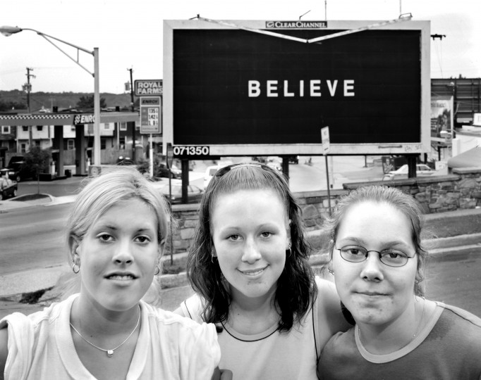 "Western High school students in front of Hickory St. billboard, near 41st. St. in Medfield: Heather Heuisler, 15, Amber Maczka, and Tracey Warren. Heather: ""I believe in God. It would be better if it had more information instead of just 'Believe.' I think they need to lock the drug dealers up. My mom keeps me from going down that path because she lost everything she had because of drugs. I live with my father. She was in jail, clean for two years, and still came out and did drugs. She's going to be like that until the day she dies."" Amber: ""I believe in myself and my friends. You don't know what it's talking about. Believe what? You can't solve the drug problem. As long as they sell weed, they're gonna do weed. As long as there's drugs, there's gonna be a drug problem. I see my friends who dropped out of school and are going nowhere in life. I see all these junkies around this neighborhood and I don't want to be like that."" Tracey: ""I believe in myself. God hasn't helped me yet. It's just there. It doesn't give you any meaning. My brother and my Dad are both on drugs. I live with my aunt and uncle. My mom is dead. I never knew her. My dad just got out of jail, but he's back on it (drugs) again. We don't talk. I've watched my brother go through being on drugs and it scares me. I don't want a thing to do with it."""