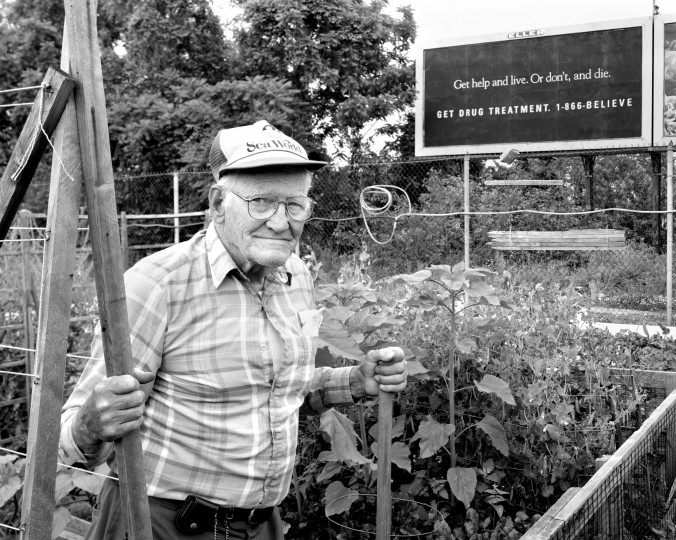 "Ed Ash, 78, working in the Carroll City Farms Garden, on S. Monroe St. in southwest Baltimore. Ash: ""I believe in God. I take things as they come. The only thing I can say about the billboard is, if you believe in yourself enough, get help. Sometimes people can't do what they want to by themselves...About gardening, if you plant it, take care of it. Without the proper care, it's not going to amount to anything. That applies to people, too. Everything needs care."""