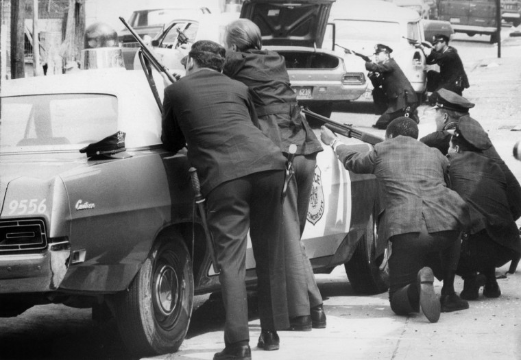 In April 1970, police with shotguns and pistols drawn crouched behind squad cards in the 1700 block North Aisquith Street as other police prepared to enter a house there. Police said they seized weapons in a car in the same block. (Lloyd Pearson/Baltimore Sun)