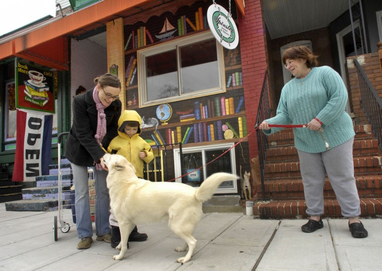 Kelly Dolde and her son Liam Dolde visit with Carla Rattini's dog, Nikki, on the vibrant commercial strip of Harford Road that has businesses such as the Red Canoe Bookstore and Cafe. (Amy Davis/Baltimore Sun file/April 3, 2008)