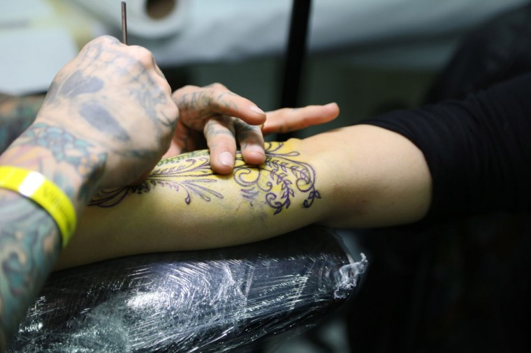 Baltimore's own Kike Castillo of Brightside tattoos Jina Kim, 25, for the second time at the Baltimore Tattoo Convention this past weekend. Over one hundred tattoo artists came from around the country to participate in the annual event. (Kaitlin Newman/Baltimore Sun)