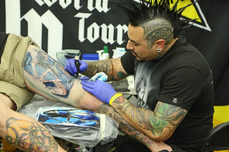 Curtis Young, 27, of VA Beach gets a thigh piece tattooed by Inked Mag cover boy Roman at the Baltimore Tattoo Convention this past weekend. Over one hundred tattoo artists came from around the country to participate in the annual event. (Kaitlin Newman/Baltimore Sun)