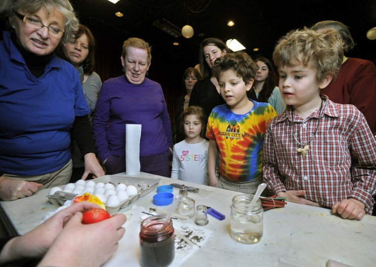 Students are captivated as Halnyn Mudryi (hands at left) demonstrates pysanky egg decoration at the Creative Alliance. (Algerina Perna/Baltimore Sun)