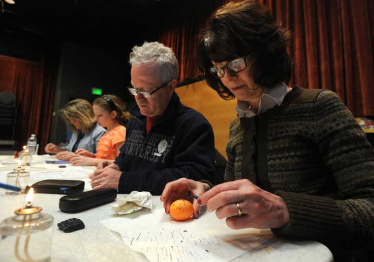 Sandy and Gary Quinlivan,right, from Pittsburgh, PA, took the pysanky egg decorating class while visiting their daughter in Baltimore. Each time the raw egg is dipped into a new color, the students then draw on the egg with wax. The color under the wax will not change when the egg is dipped in a new color. (Algerina Perna/Baltimore Sun)