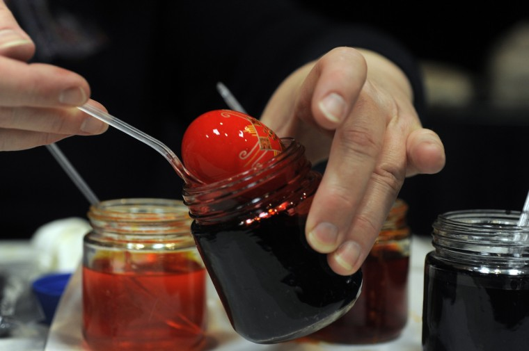 Halyna Mudryj dips the egg in a red dye. She works from lighter to darker colors. Using darker colors first would not allow brighter colors to show. (Algerina Perna/Baltimore Sun)