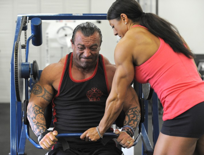"Nikki Johnston ""spots"" her husband David as he works out at the Colosseum Gym in Columbia. They are preparing for a bodybuilding tournament. (Lloyd Fox/Baltimore Sun)"